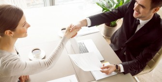 Smiling female and male business leaders handshaking over desk after or before signing contract in office. Happy businesswoman congratulating businessman with concluding profitable agreement. Top view